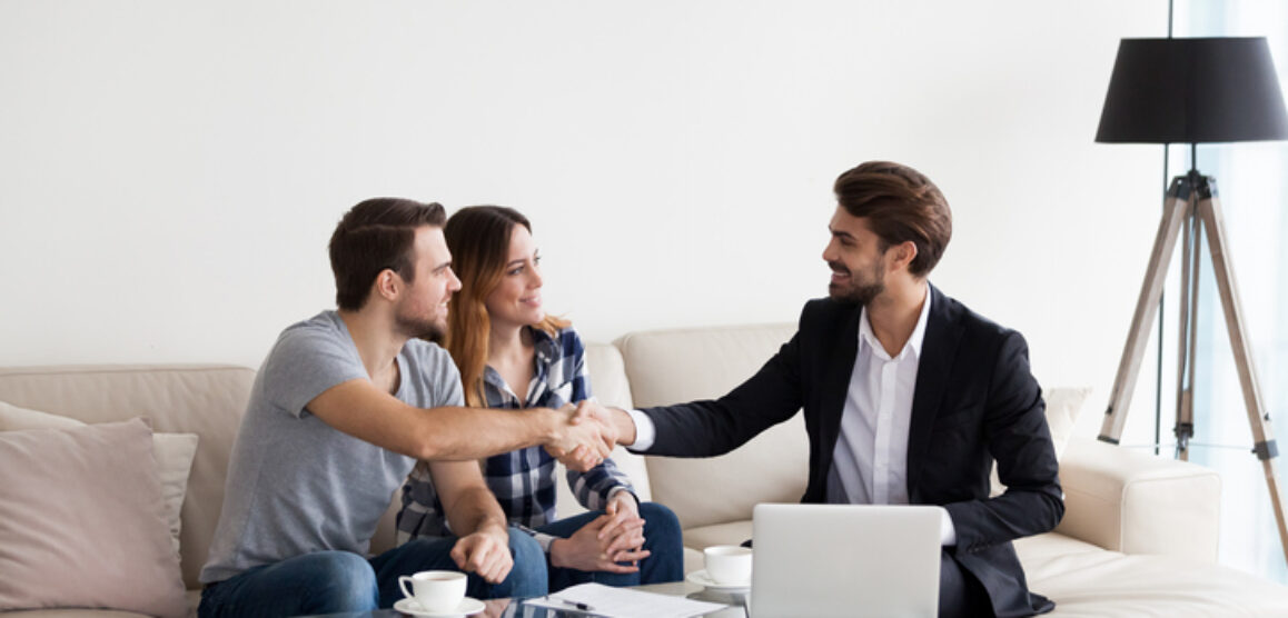 Young couple, family making deal with realtor, interior designer